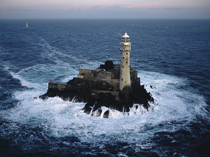 Catamaran 'Jet Services V' is the first multihull to round the Fastnet Rock Lighthouse during the Quebec-Saint Malo Race 1987.