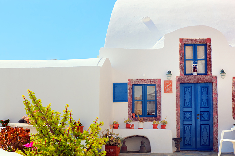 Traditional Greek house with blue door and windows, Santorini res