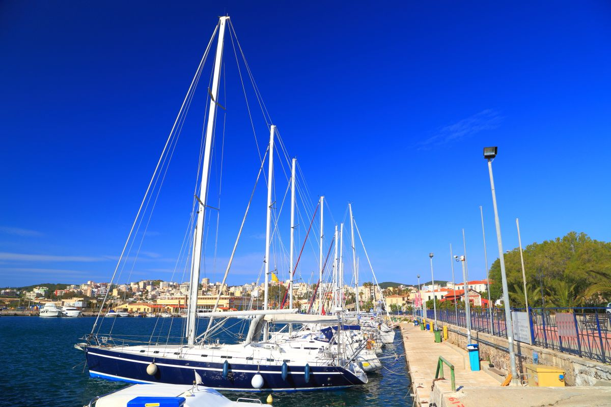 Sunny pier with sail boats at anchor in Lavrion harbor, Attica, Greece